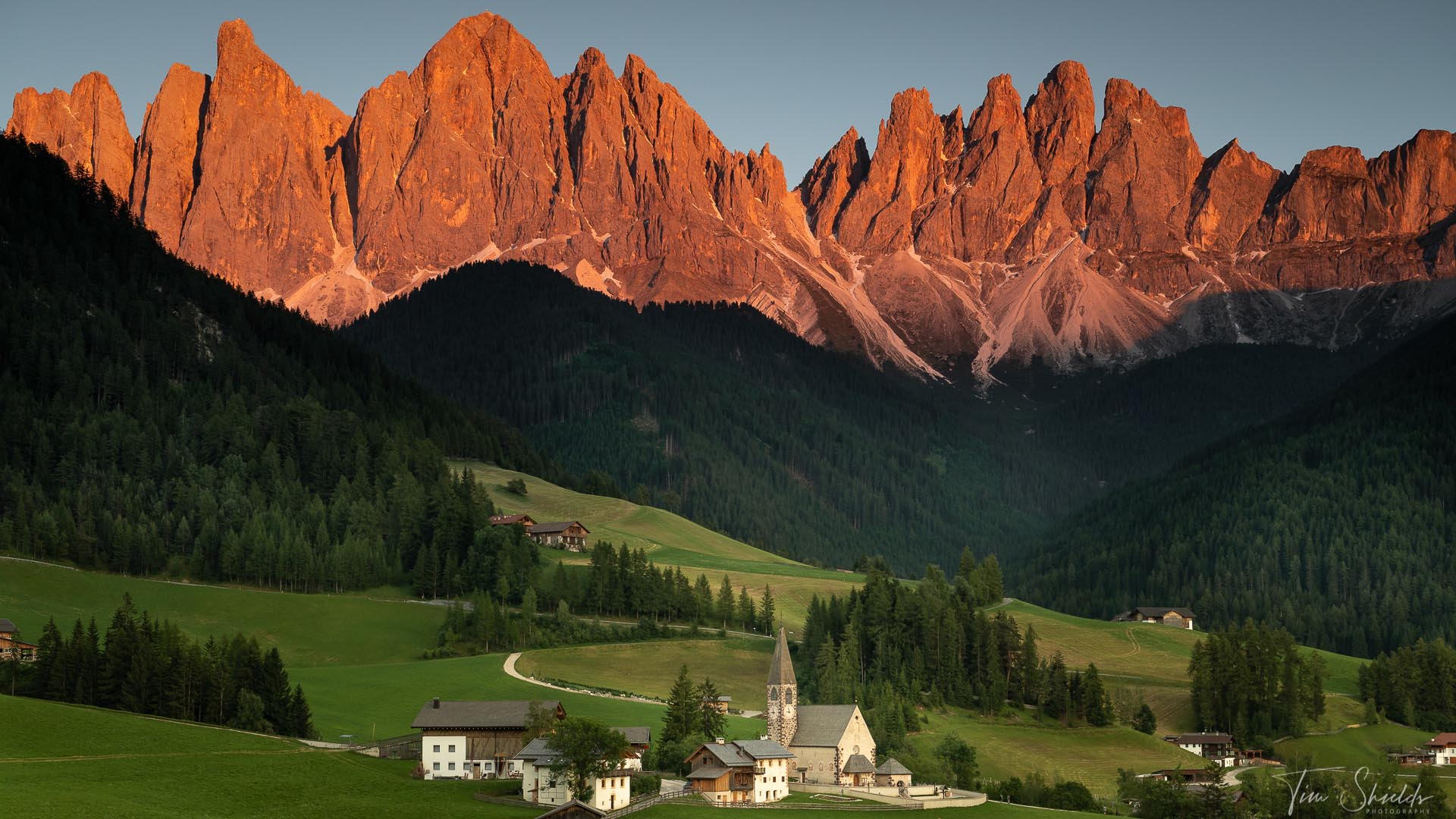 A photograph of a small village just below an iconic mountainous landscape