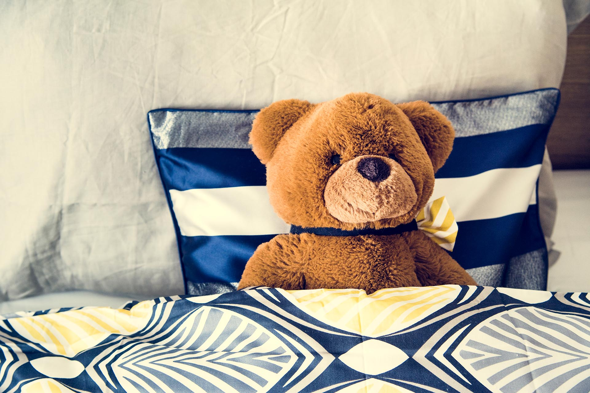 A photo of a Teddy bear on the bed