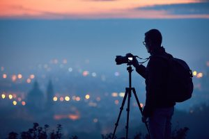 A photographer with his tripod overtop the city.